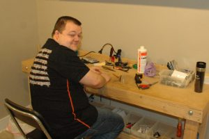 Brandon Hobbs, Owner of Custom Kraze Phone Repair, at His Workbench